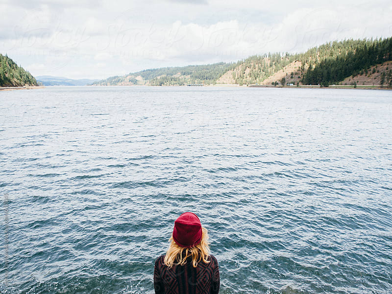 Girl in Beanie looking at lake with mountains in background by Jeremy Pawlowski for Stocksy United