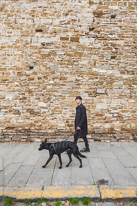 Young Man with Black Dog Walking on a Sidewalk by Giorgio Magini for Stocksy United