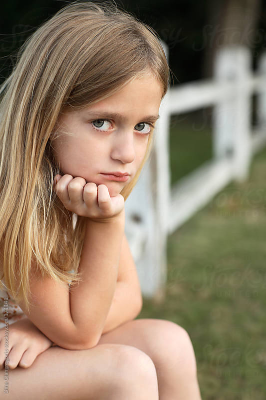 Young girl with long hair sitting outdoors with serious expression by Dina Giangregorio for Stocksy United