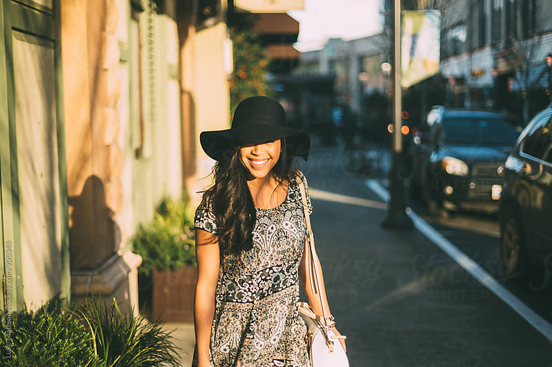 Smiling Young Woman In Sun Hat Outside Shopping Mall by Luke Mattson for Stocksy United