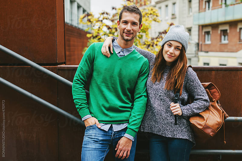 Young beautiful couple standing on stairs in outdoors. by BONNINSTUDIO for Stocksy United