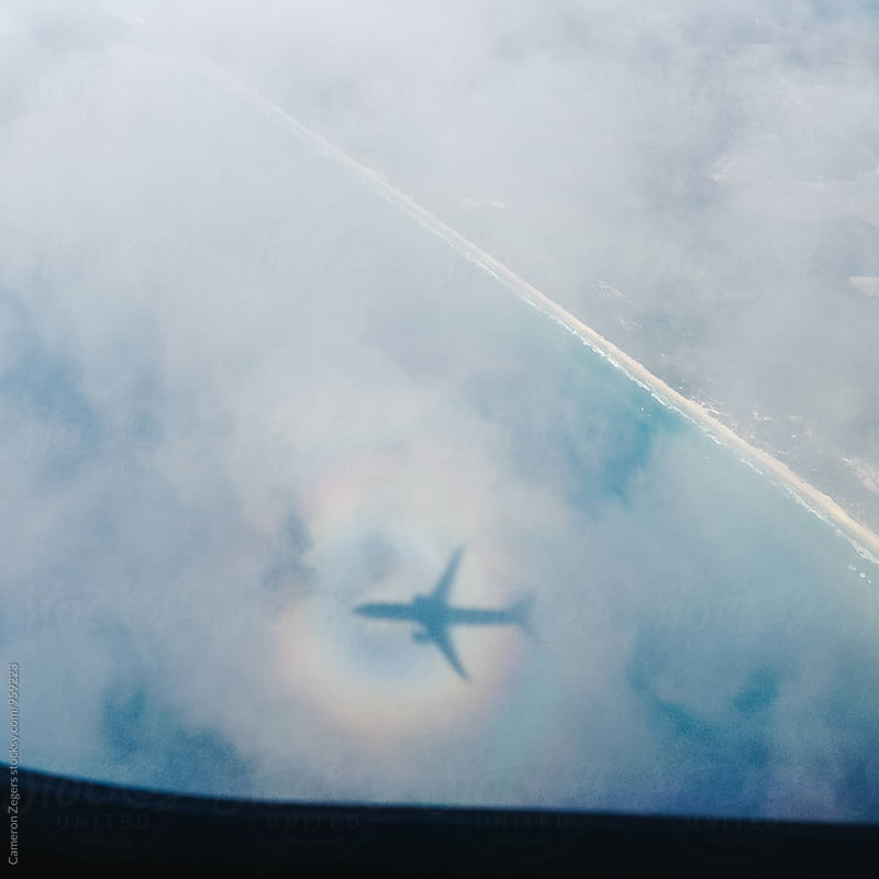 shadow of airplane on clouds over ocean by Cameron Zegers for Stocksy United