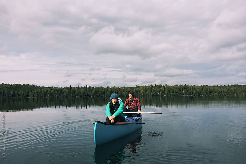 Canoe on a still lake by Jeff Marsh for Stocksy United