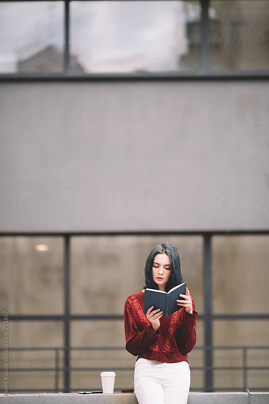 real young woman reading book on the roof  by Vesna for Stocksy United