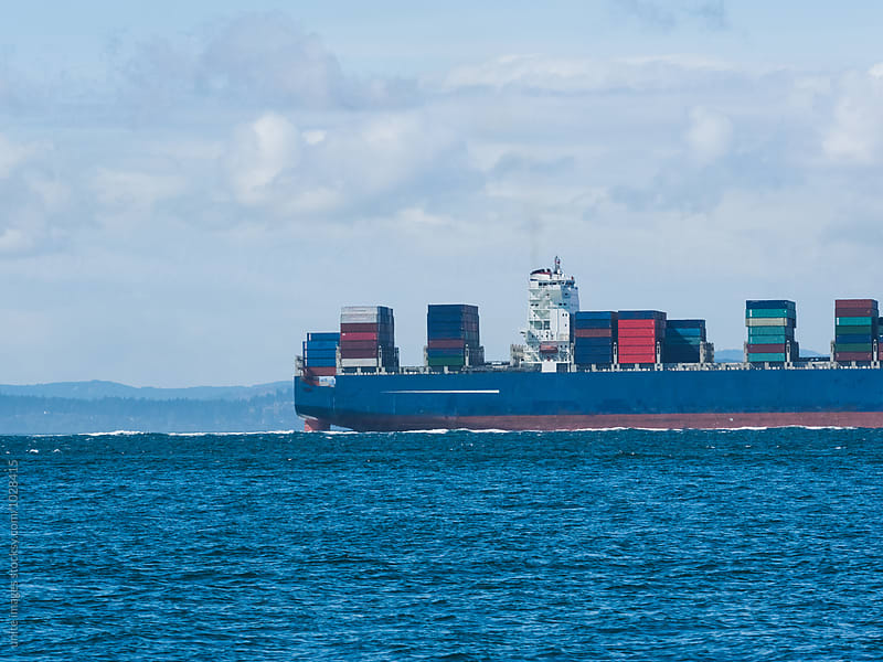 cargo ship on the ocean with coast in background by unite images for Stocksy United