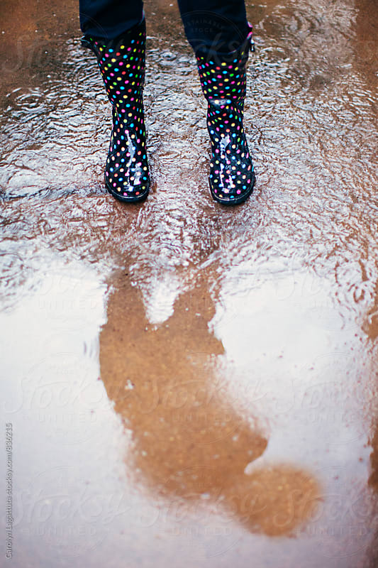 Rain boots splashing in a puddle with a shadow by Carolyn Lagattuta for Stocksy United