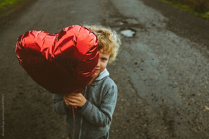 Little Boy Holding Heart Balloon by Bryan Rupp for Stocksy United