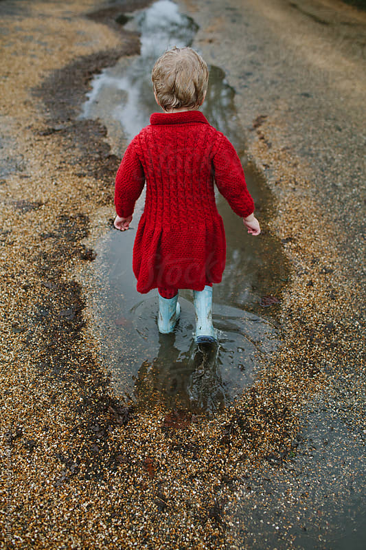 Back of child walking through puddle. by Julia Forsman for Stocksy United