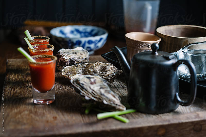 Oysters and shooters. by Darren Muir for Stocksy United