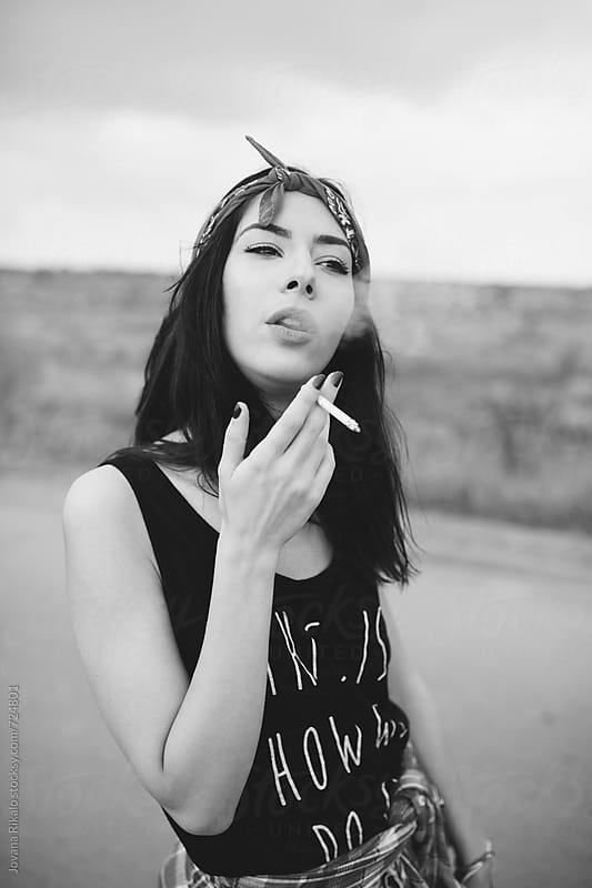 Black and white portrait of a young woman with a cigarette by Jovana Rikalo for Stocksy United