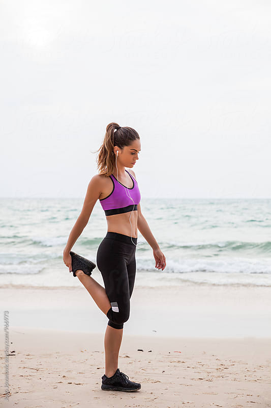 Woman stretching at the beach - fitness outdoors by Jovo Jovanovic for Stocksy United