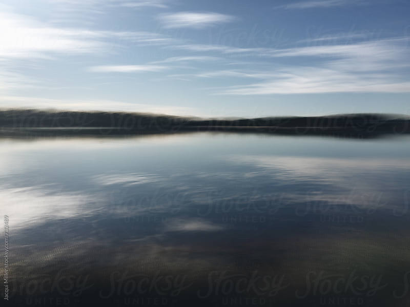 Movement shot of a river with cloud reflections on water by Jacqui Miller for Stocksy United