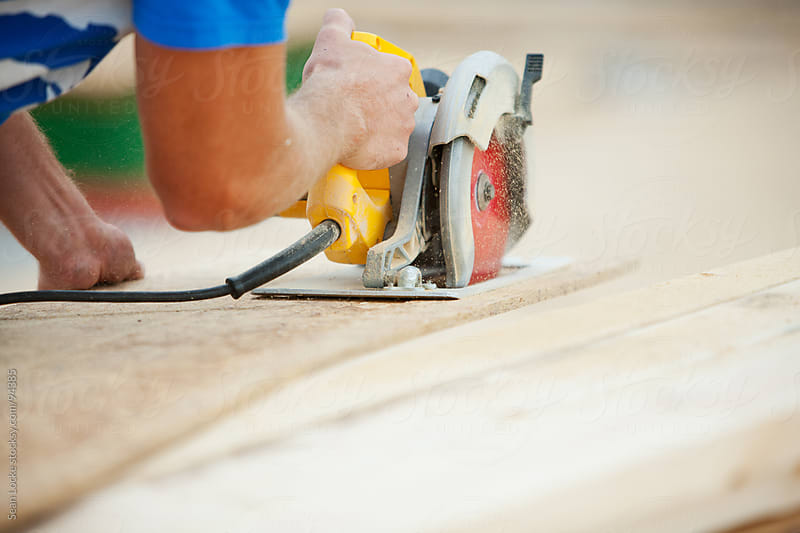 Construction: Carpenter Cutting Panel with Saw by Sean Locke for Stocksy United