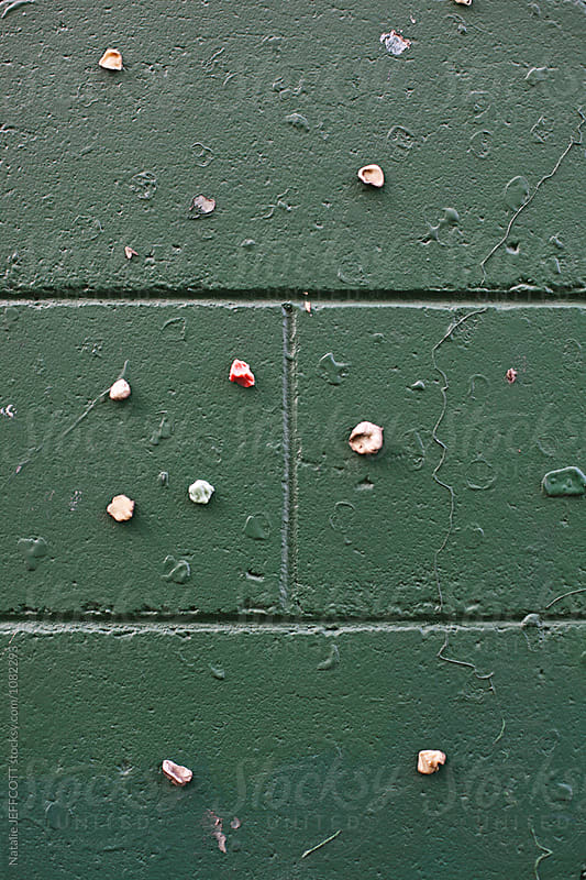 Green cement block wall with colourful chewing gum by Natalie JEFFCOTT for Stocksy United