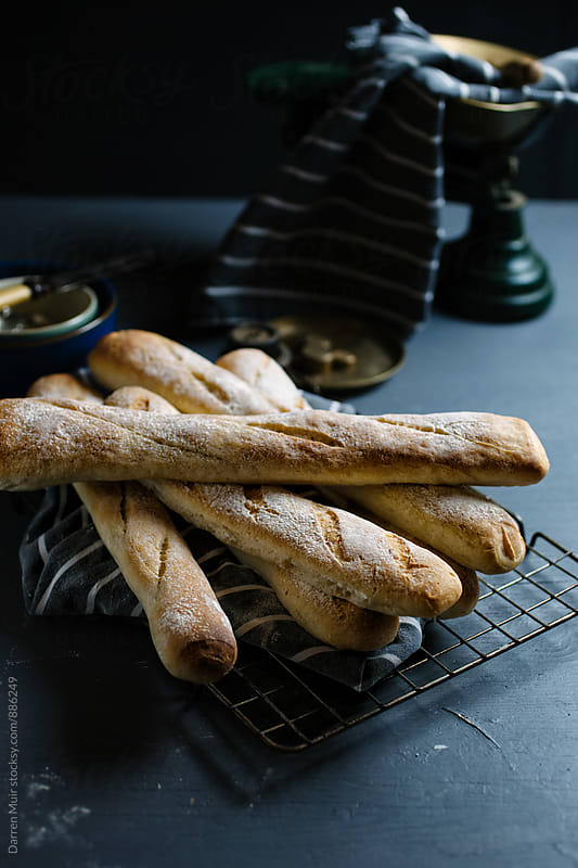 Freshly baked baguettes on a wire cooling rack.  by Darren Muir for Stocksy United