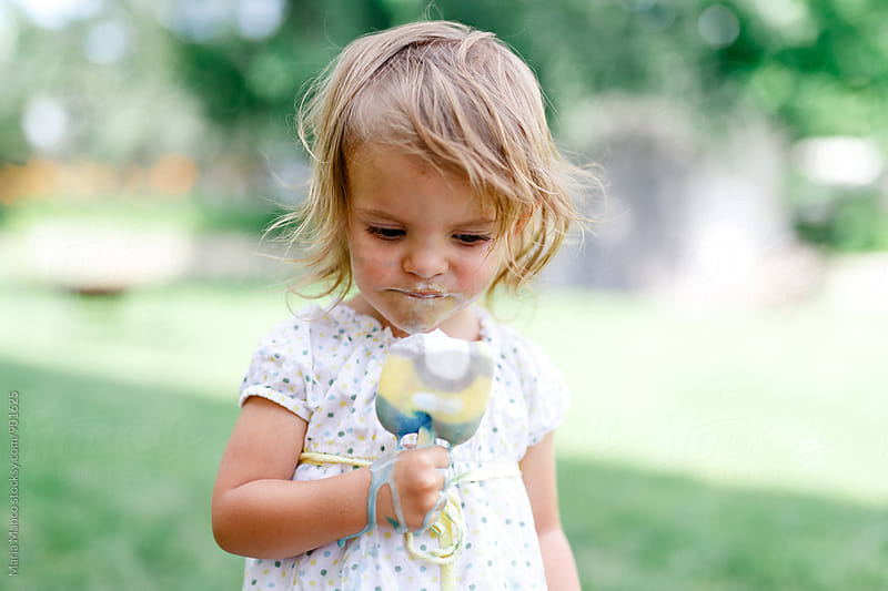 Little girl eats melting ice cream and makes a mess by Maria Manco for Stocksy United