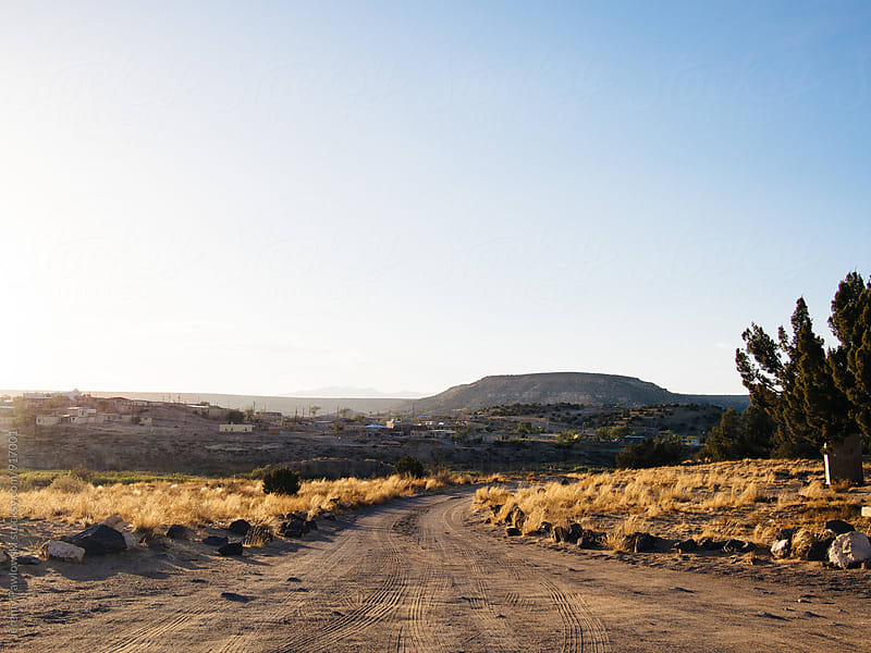 Desert dirt road leading to small town. Golden sunrise. by Jeremy Pawlowski for Stocksy United