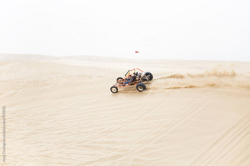 A sand rail speeding along the ridge of a sand dune by Amy Covington for Stocksy United