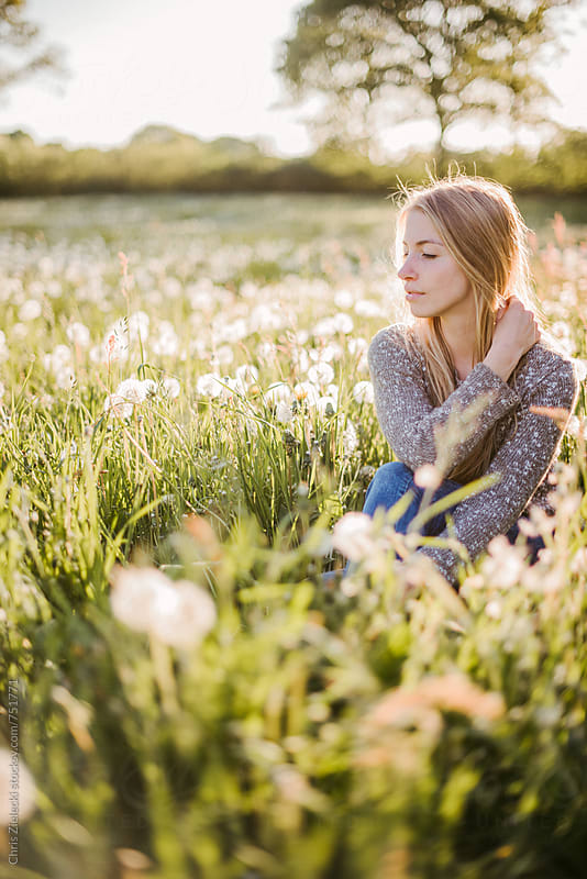 a girl is sitting in a dandelion meadow by Christian Zielecki for Stocksy United