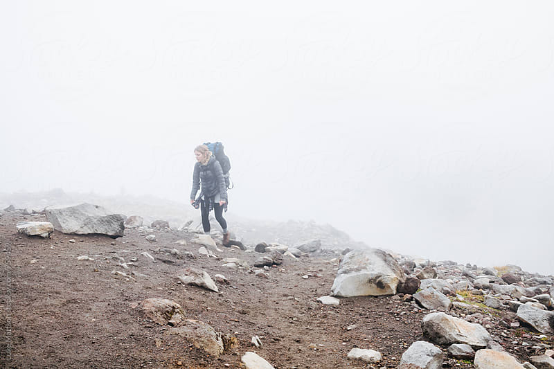 Young Female Backpacker Climbing Up Rocky Mountainside Through Fog by Luke Mattson for Stocksy United