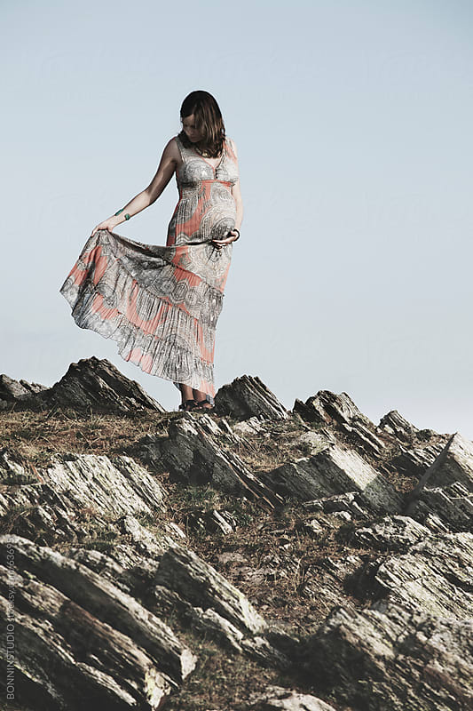 Pregnant woman on rocks landscape holding her dress.  by BONNINSTUDIO for Stocksy United