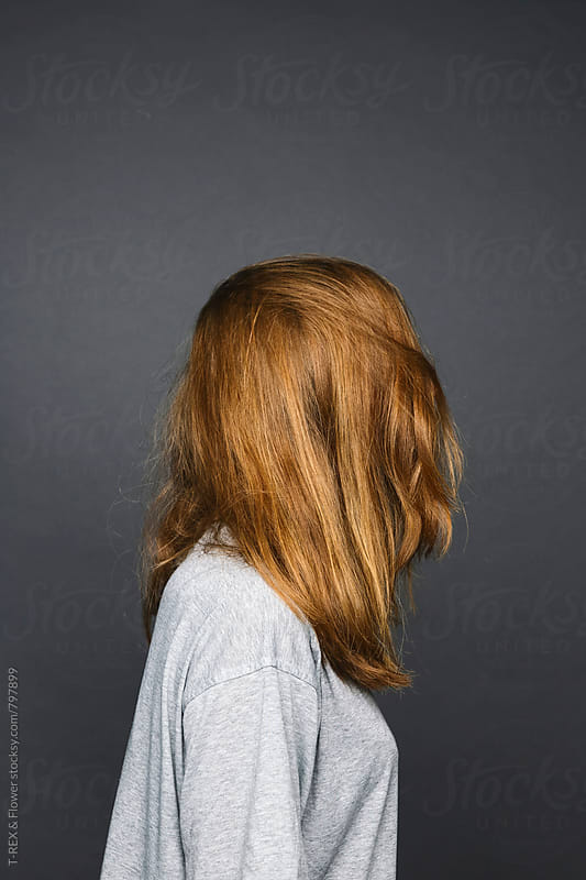 Photo of redheaded woman, face covered with hair by T-REX & Flower for Stocksy United