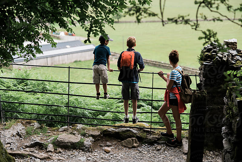 three kids on a gate in the countryside on Wales by Léa Jones for Stocksy United