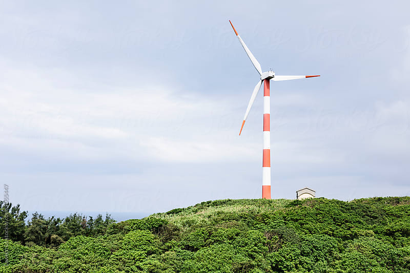 Windmill in forest against of cloudy sky by Lawren Lu for Stocksy United