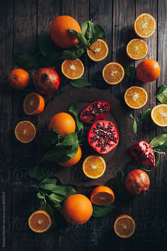 Oranges and pomegranate on wooden table by Nataša Mandić for Stocksy United