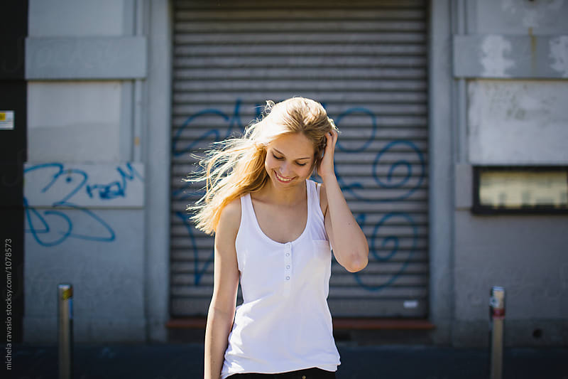 Smiling girl walking around the city in summer by michela ravasio for Stocksy United