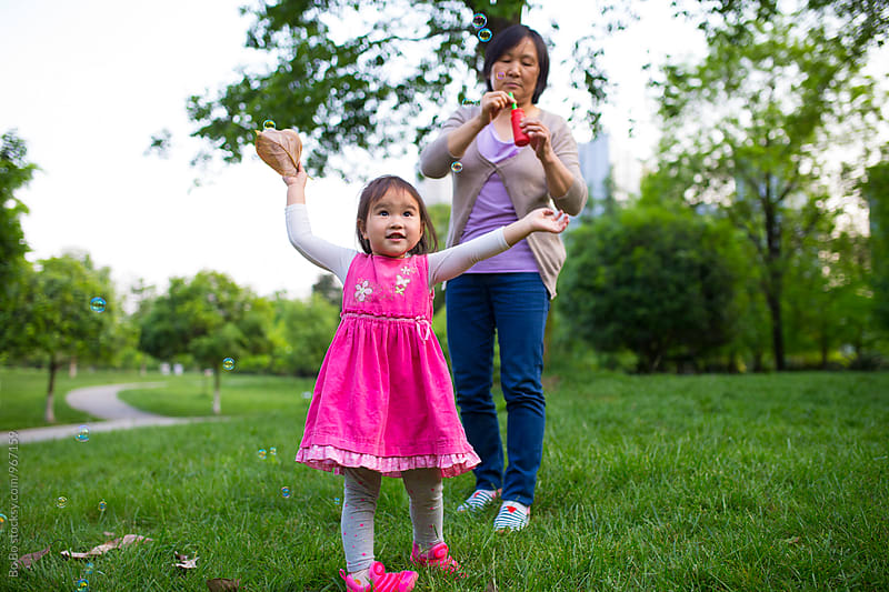 lovely little asian girl having good time outdoor with her grandmother by Bo Bo for Stocksy United