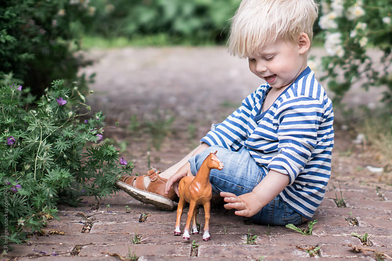 Toddler playing in a garden with a toy horse by Per Swantesson for Stocksy United