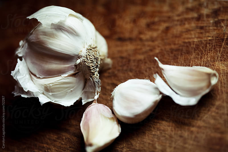 Garlic bulb on a cutting board by Carolyn Lagattuta for Stocksy United