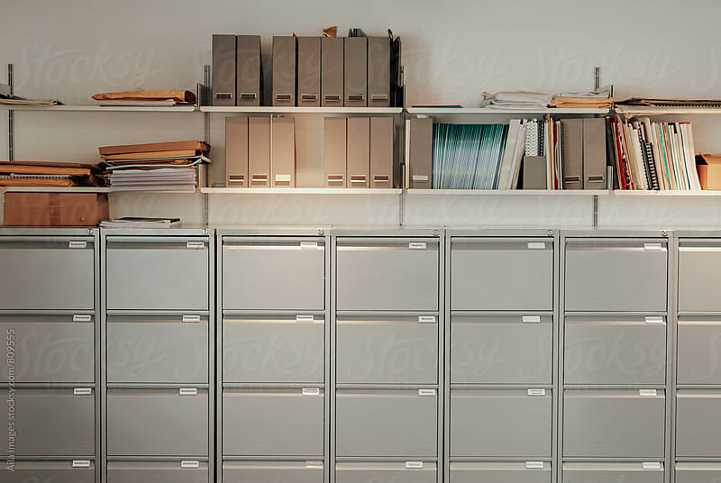Stylish filing cabinet office storage in empty offive after hours by Aila Images for Stocksy United