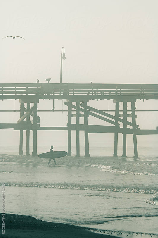 Man with surfboard running into the ocean next to pier. by RZ CREATIVE for Stocksy United