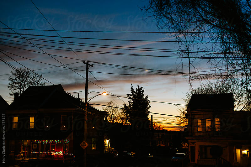 A city neighborhood decorated with Christmas lights at twilight. by Holly Clark for Stocksy United