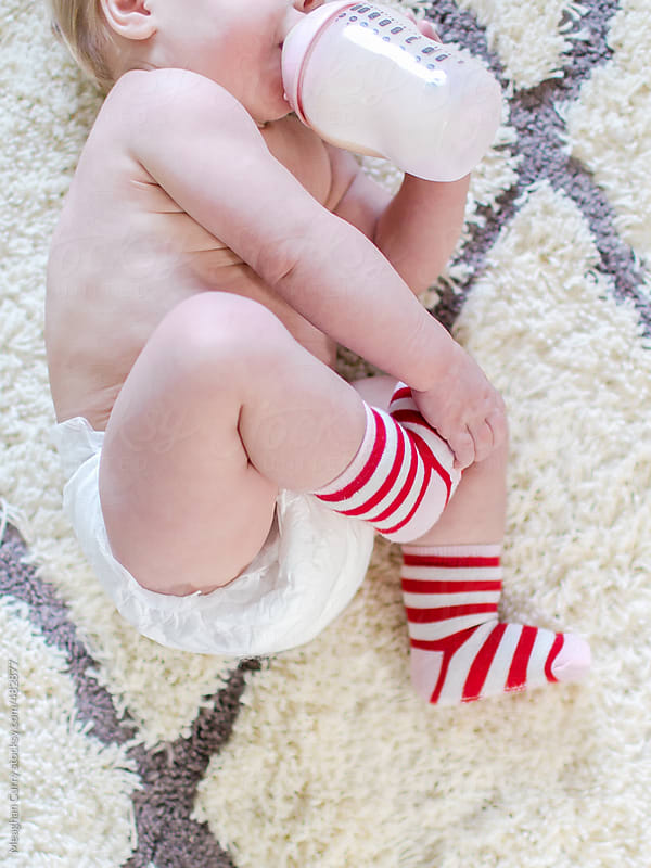 baby drink a bottle wearing striped Christmas socks by Meaghan Curry for Stocksy United