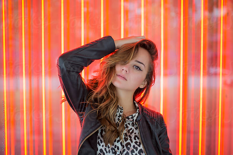 Young beautiful brunette woman in front of a colorful lights by Maja Topcagic for Stocksy United