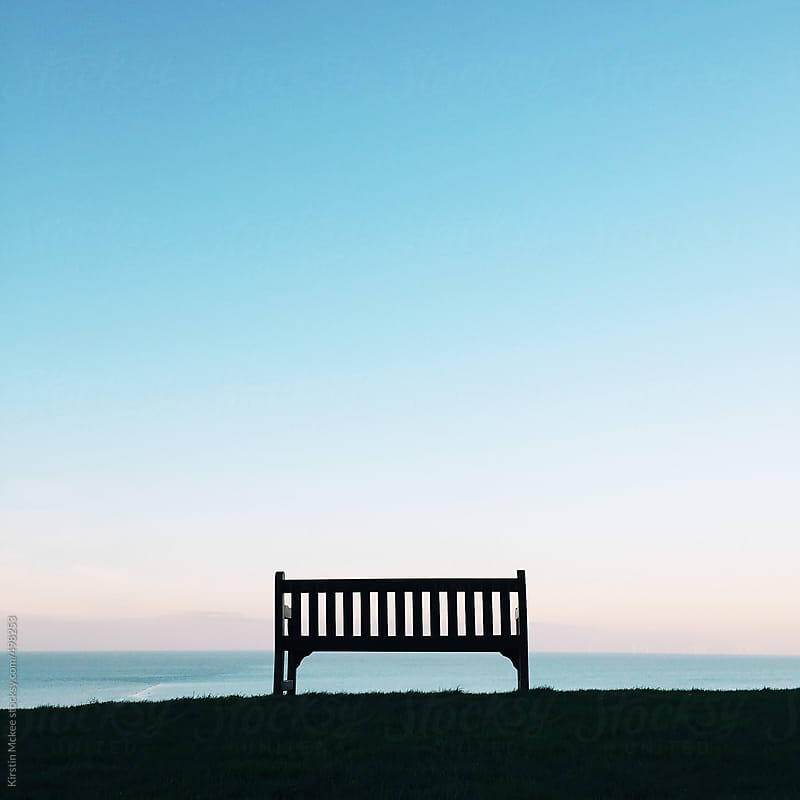 A bench with a view of the sea at sunset by Kirstin Mckee for Stocksy United