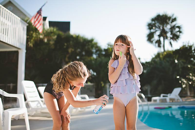 girls applying sunscreen by Erin Drago for Stocksy United
