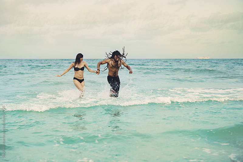 Playful Couple Running in the Surf by Stephen Morris for Stocksy United