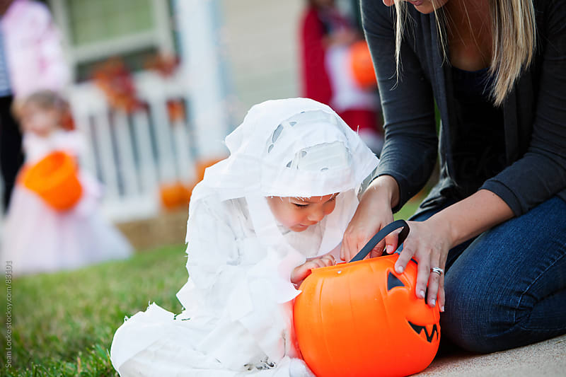 Halloween: Boy Looks In Bucket To See Candy by Sean Locke for Stocksy United
