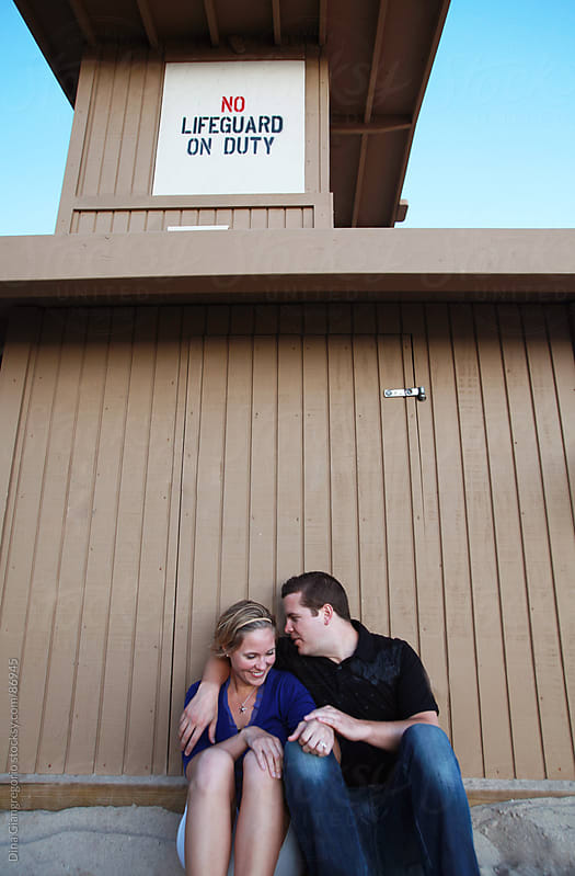 Happy young couple sitting up against beach lifeguard station by Dina Giangregorio for Stocksy United