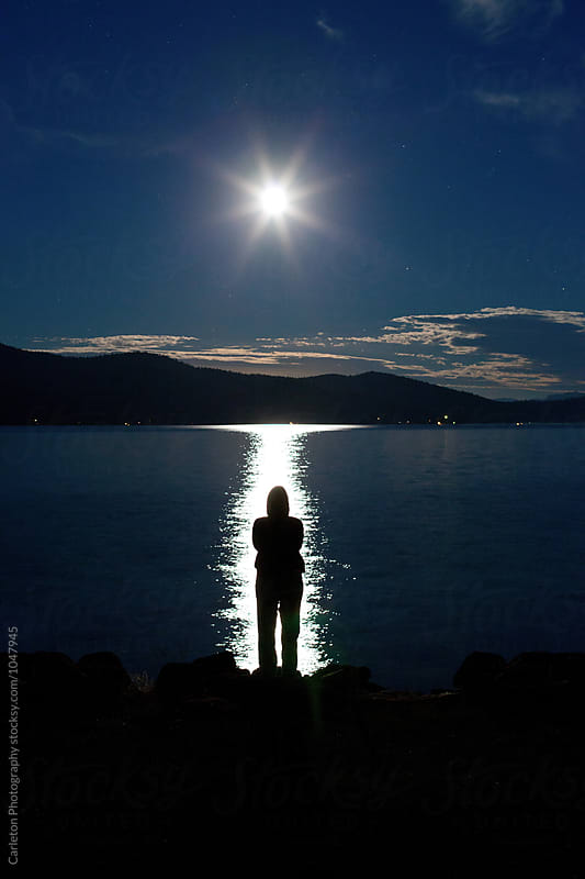 Lone figure stands on the edge of a lake during a newly risen full moon by Carleton Photography for Stocksy United