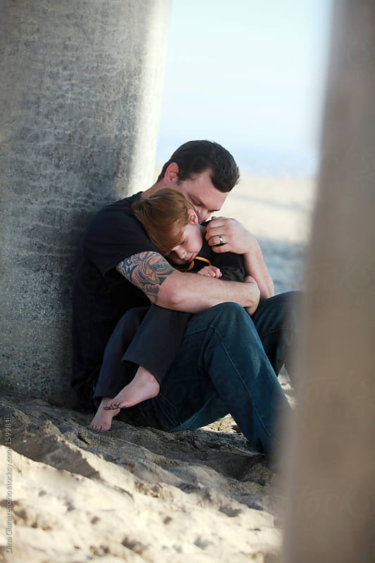 Father with tattoos holding toddler at beach by Dina Giangregorio for Stocksy United