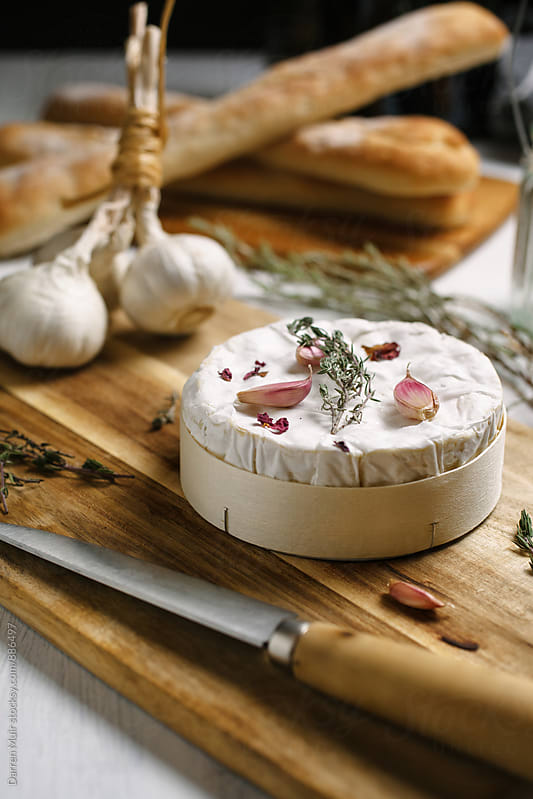 Camembert cheese on a cutting board with bread in the background. by Darren Muir for Stocksy United