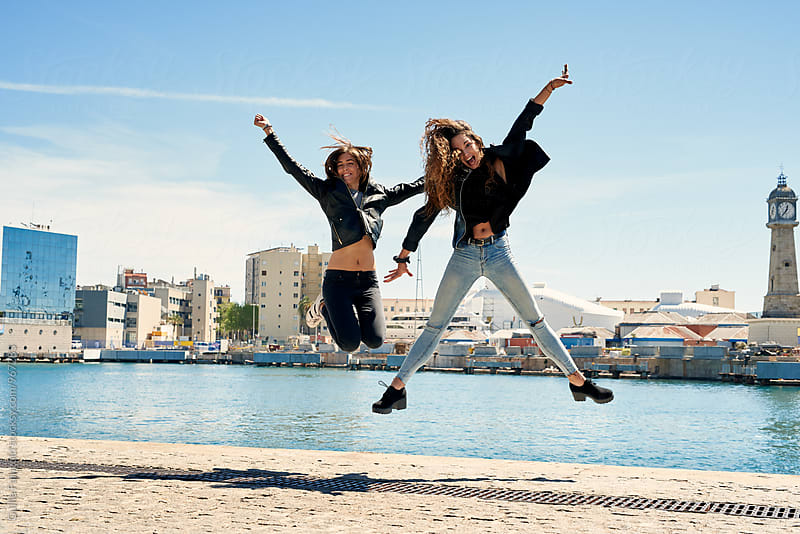 Two cheerful girlfriends jumping at pier by Guille Faingold for Stocksy United