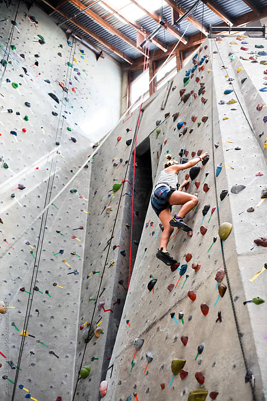 Young girl climbing to the top of a  rock wall by Carolyn Lagattuta for Stocksy United