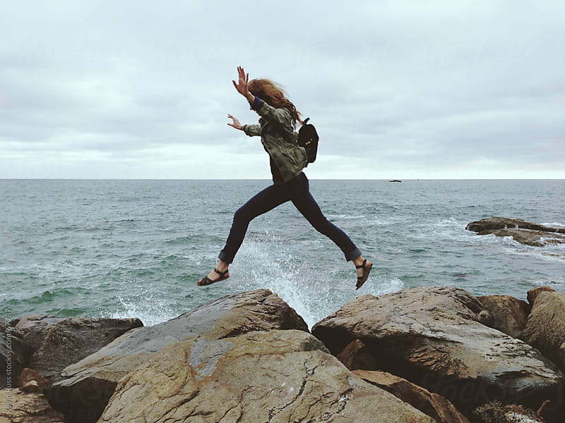 Woman Jumping on Jetty Rocks by Kevin Russ for Stocksy United