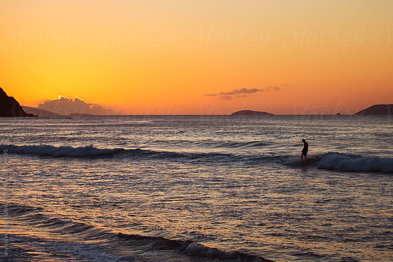Surfer on the sea at sunset by anya brewley schultheiss for Stocksy United
